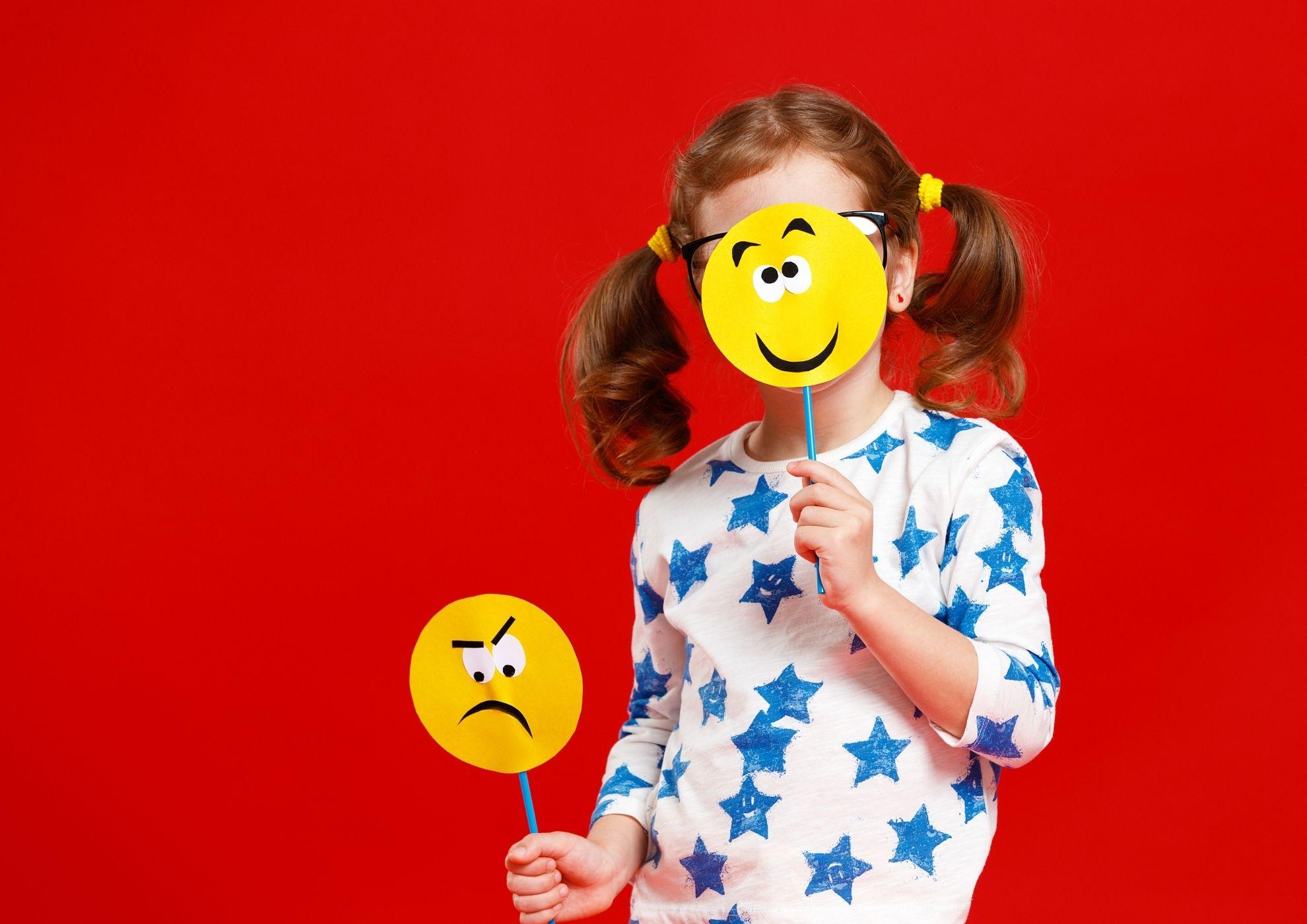 Una niña juega con dos caretas que representan la emoción de la alegría y la tristeza.