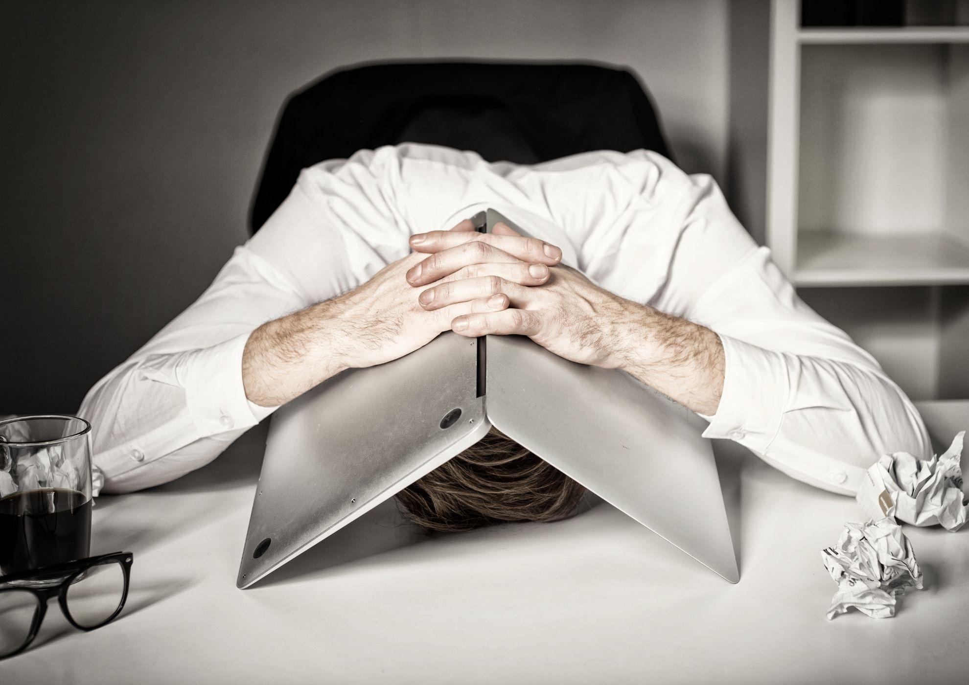 Un hombre esconde su cabeza bajo el portatil, desesperado